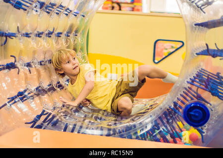 Cute little boy, playing in Zorb a rolling plastic cylinder ring with a hole in the middle, intdoor - Stock Photo