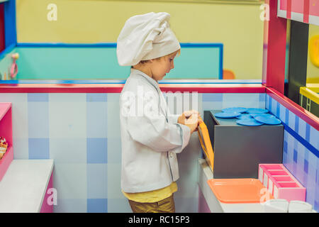 The boy plays the game as if he were a cook or a baker in a children's kitchen - Stock Photo