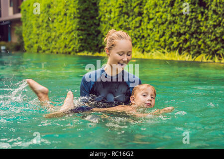 Woman swimming instructor for children is teaching a happy boy to swim in the pool - Stock Photo