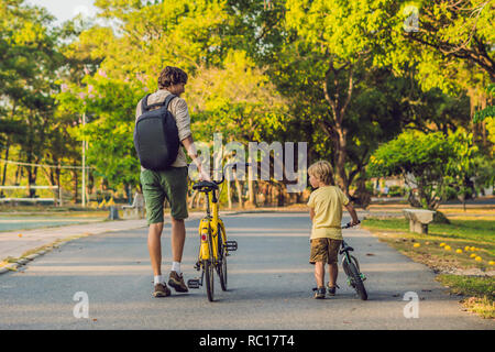 Happy family is riding bikes outdoors and smiling. Father on a bike and son on a balancebike - Stock Photo