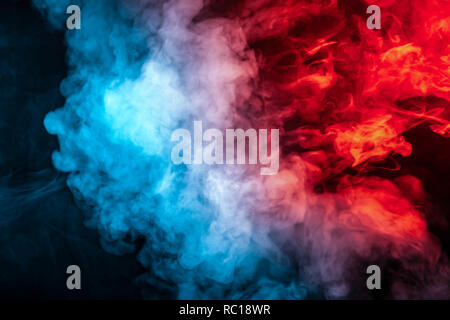 Clouds of isolated colored smoke: blue, red, orange, pink; scrolling on a black background in the dark close up. - Stock Photo
