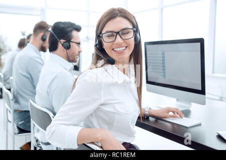 young call center employee works in a modern office - Stock Photo