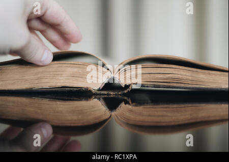 Hands folded in prayer on a Holy Bible in church concept for faith, spirtuality and religion - Stock Photo