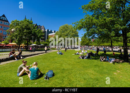 Crowds of locals and tourists enjoy summer and hot weather sunbathing and having picnics or ice cream at the Rhine Garden park. Rheingarten Cologne. - Stock Photo