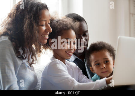 African parents and children laughing doing online shopping on l - Stock Photo