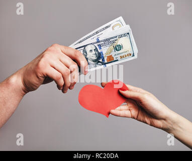 a Male hand holding a pack of money trying to buy a red hearts from female hand - Buying love concept - Stock Photo