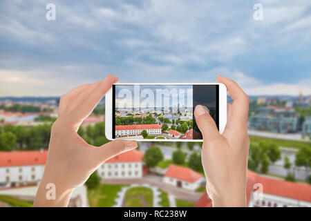 A tourist is making a photo of Aerial panoramic view of the capital of Lithuania - Vilnius on a mobile phone - Stock Photo