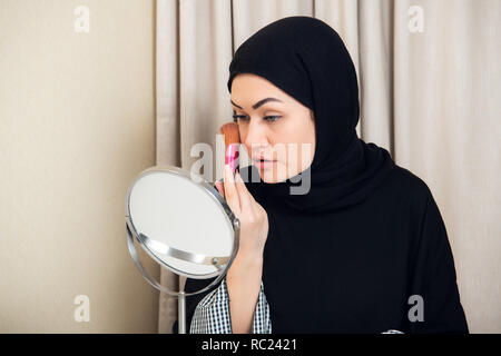 Beauty muslim woman with hijab applying makeup. Beautiful girl looking in the mirror and applying cosmetic. Girl gets blush on the cheekbones. - Stock Photo