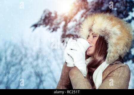 Calm contented woman gladly drinks hot coffee among snow-covered trees, enjoys the winter holidays walking in the park in frosty sunny day - Stock Photo