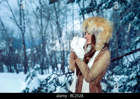 Calm contented woman gladly drinks hot coffee among snow-covered trees, enjoys the winter holidays walking in the park - Stock Photo