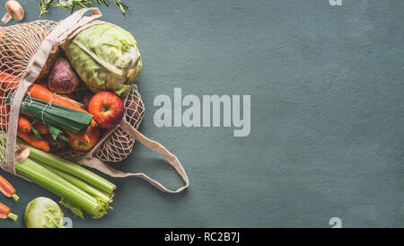 Various farm organic vegetables from local market in net string reusable bag on rustic background, top view with copy space for your design, banner. C - Stock Photo