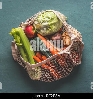 Various farm organic vegetables from local market in net string reusable bag on rustic background, top view . Clean and healthy food concept. - Stock Photo