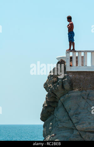 Mazatlan / Mexico - July.6.2006: Man, cliff diver standing on the edge of the rocky tower and praying before the jump. Sunny day, blue sky. - Stock Photo