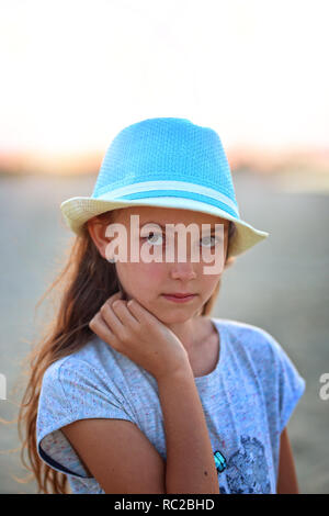 young girl in a hat on a sunny day at the beach - Stock Photo