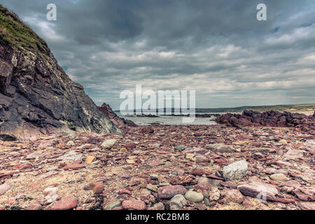 Beautiful scenery of dramatic Pembrokeshire coastline,South Wales,Uk.Rock formations on beach exposed during low tide and moody sky over sea.Scenics. - Stock Photo