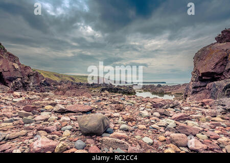 Beautiful scenery of dramatic Pembrokeshire coastline,South Wales, Uk.Stones and puddle on rocky beach during low tide.Moody sky over horizon.Scenics. - Stock Photo
