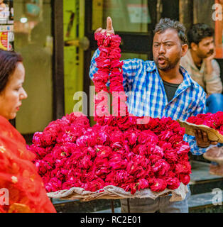 Vrindavan, India / February 22, 2018 - Man sells red flower leis from his street table - Stock Photo