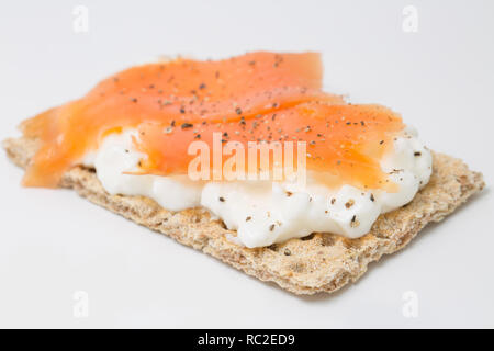 A rye bread cracker spread with fat free cottage cheese and farmed, smoked salmon slices with black pepper. On a white background. England UK GB - Stock Photo