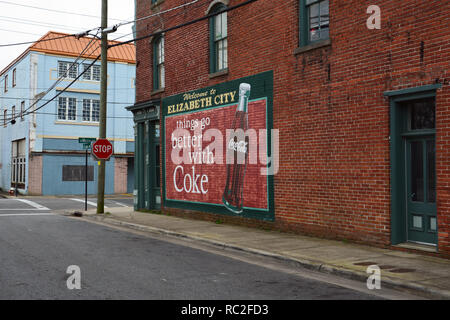 A classic sign for Coca Cola on the side of an old corner store in the historic downtown of Elizabeth City North Carolina. - Stock Photo