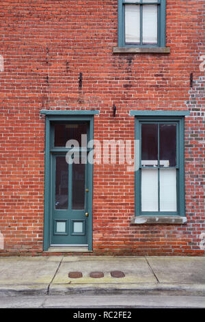 An old wood frame door and window painted green against a weathered red brick wall in the small town of Elizabeth City, North Carolina. - Stock Photo