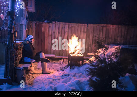 Winter thoughtful lonely teenager boys missing and getting warm at fire in night snowy countryside - Stock Photo