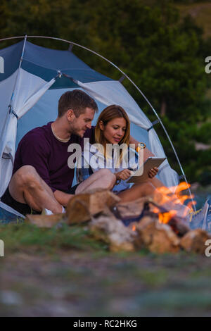 Young couple working on a tablet and enjoying the mountain view with bonfire in the sunset in the forest - Stock Photo