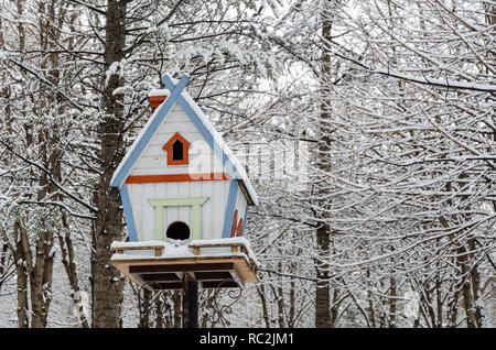 Wooden birdhouse hanging outdoors in winter covered with snow - Stock Photo