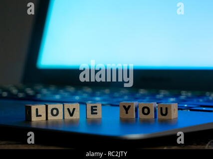 Conceptual image of text Love you in wood blocks on computer with mood romantic screen light background in Valentines day internet connection technolo - Stock Photo