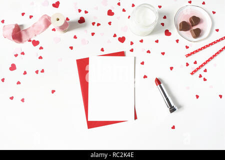 Valentines day, wedding still life scene. Candle, paper confetti, chocolate hearts, lipstick and blank greeting card mockup on white table background. Love concept. Flat lay, top view. - Stock Photo