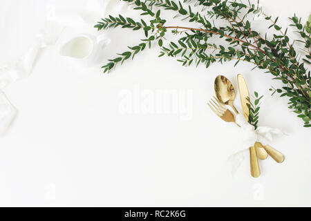 Festive wedding, birthday table setting with golden cutlery, eucalyptus parvifolia, silk ribbon and milk pitcher on white table background. Rustic restaurant menu concept. Flat lay, top view. Empty space. - Stock Photo