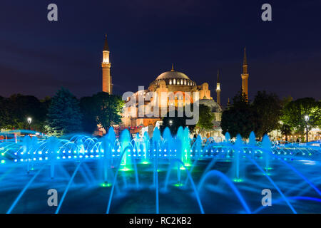 The Sultan Ahmad Maydan water fountain lit up with the Hagia Sophia museum in background at dusk, Istanbul, Turkey - Stock Photo