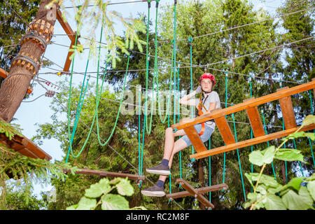 Teenager boy wearing safety harness sitting on a hanging rope bridge at a ropes course in outdoor treetop adventure park taking a break - Stock Photo