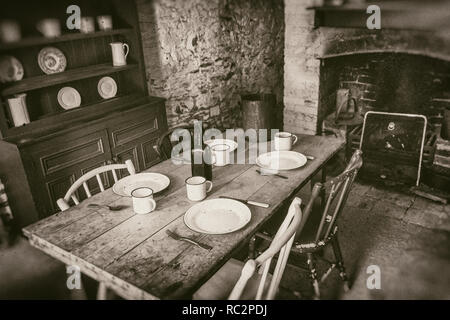 Poor peasants interior from 19th century, dining room with set wooden table and fireplace, sepia style photography - Stock Photo