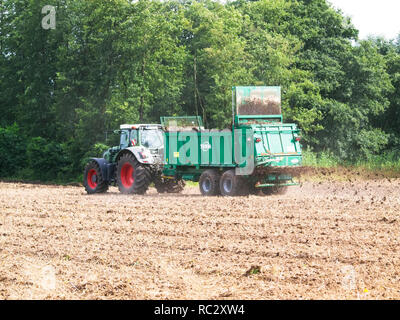 Farmer on his tractor coupled with a manure spreading trailer firtilizing his acre near Barum, Elbmarsch, Niedersachsen, Germany. - Stock Photo