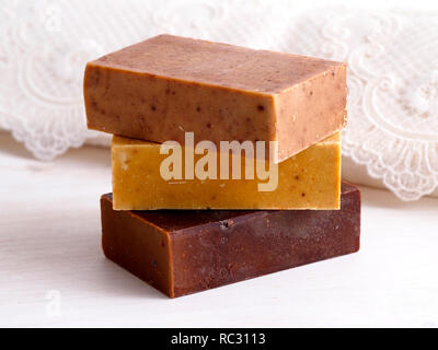 Natural soap bars and lace towel on white wooden background - Stock Photo