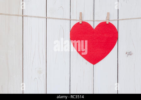 Red heart hanging on white wood  background with copy space. - Stock Photo
