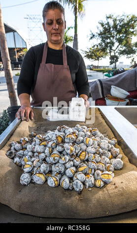 Roasted sweet chestnuts on sale at an open air stall. - Stock Photo