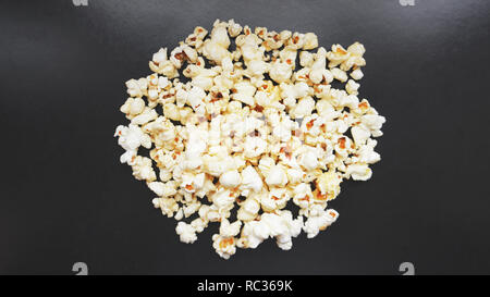 Heap of classic salty popcorn on black background. Concept cinema or food - Stock Photo