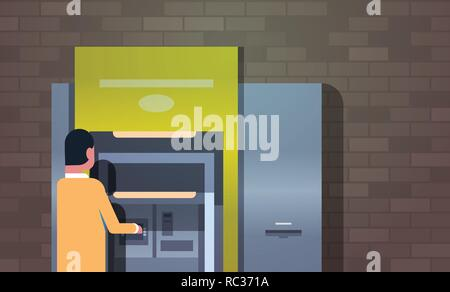 man withdrawing cash via ATM automatic teller machine payment terminal businessman getting money or paying debts outdoor banking equipment horizontal  - Stock Photo