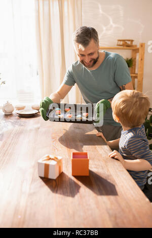 Cheerful bearded father in oven mitt taking pan with Valentines cookies out of oven and putting on table while preparing gift together with son - Stock Photo