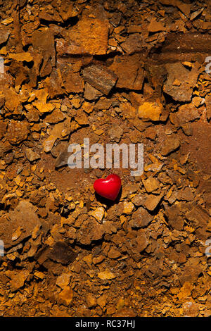Small red glass heart on surface of dry rusted metal. - Stock Photo