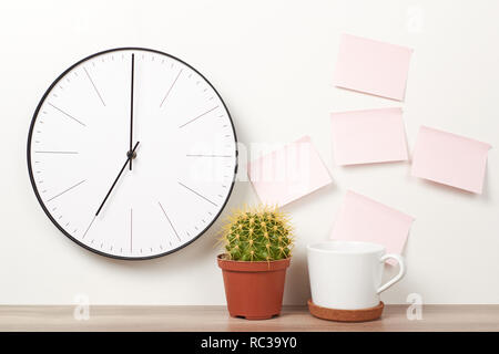 Wall clock, pink stickers, cactus and cup on white background. Workspace mock up - Stock Photo