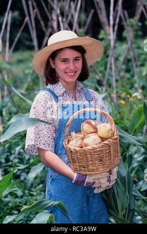 Young woman showing a basket with freshly picked onions in an organic garden. Today more than ever, backyard gardens are going organic. - Stock Photo