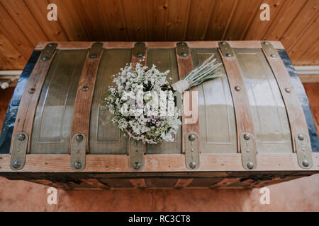 rustic bridal bouquet on a vintage wooden and iron trunk - Stock Photo