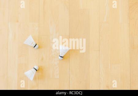 White badminton shuttlecocks on hall floor at badminton courts. - Stock Photo