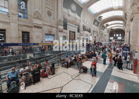 Milan, Italy - August 5, 2018: People in Milano Centrale, the central train station of Milan. Designed by architect Ulisse Stacchini, the building was - Stock Photo