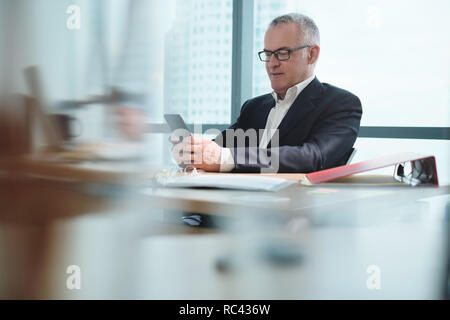 Business Man In Office Using Social Media During Working Hours - Stock Photo