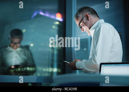 Happy Manager Using Smartphone In Dark Office At Night - Stock Photo