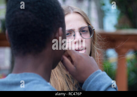 A photo of two students talking to each other in a park - Stock Photo