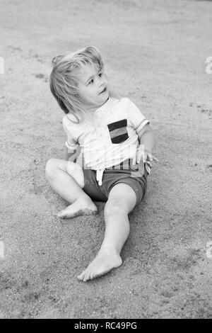 First vacation with child tips and advice. Boy little kid sit on sand. Toddler enjoy vacation at beach. Take care about safety travel child. Top activities for toddler at beach. United with nature. - Stock Photo